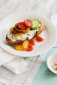 A slice of bread topped with cottage cheese, tomatoes and cucumber