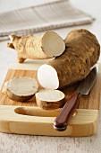Horseradish, sliced, on a chopping board