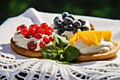 Three fruit tarts with cream, redcurrants, blueberries and mango