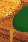 Detail einer Tischplatte mit Maserung und teilweise sichtbarer Stuhl mit grünem Sitzpolsterbezug