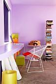 Lila getönter Raum mit geschwungener Platte an Wand in gleichem Farbton und Klassiker Stuhl aus weißem Metallgitter