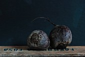 Two beetroots on a wooden crate against a dark background