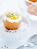 A soft-boiled egg on a bed of salt