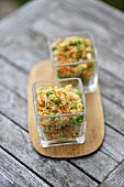 Quinoa salad with vegetables in two glass bowls