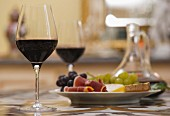 Glasses of red Bordeaux wine with plate of grapes, ham and cheese.