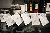 Orders on pieces of paper in a restaurant kitchen