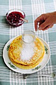 Pancakes being dusted with icing sugar served with jam