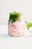 A glass of strawberry yogurt with mint granita
