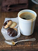 A mug of espresso served with biscuits