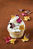 A cinnamon cupcake topped with cream and decorated with sugar leaves
