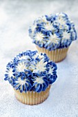 Lavender cupcakes topped with blue-and-white cream