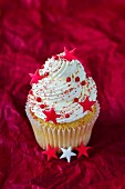 An almond cupcake topped with cream and decorated with stars