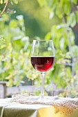 A glass of red wine on a garden table