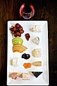 A cheese platter with fruit, jam and wine