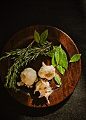 Bay leaves, rosemary and garlic on a wooden plate