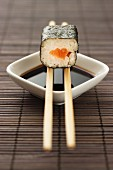 Maki sushi with salmon balanced on chopsticks over a bowl of soy sauce
