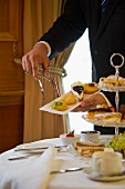 A waiter serving cakes with afternoon tea (England)