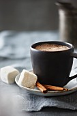 A cup of hot chocolate with marshmallows and cinnamon sticks
