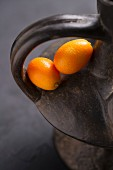 Two kumquats in the handle of a terracotta jug