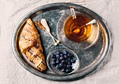 A cup of tea, croissants and blueberries on an old-fashioned tray