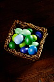 Blue and green Easter eggs in a wicker basket