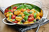 Gnocchi with tomatoes, olives, pine nuts and basil