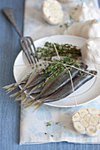 Raw sardines on a plate with thyme and garlic
