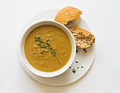 Creamer vegetable soup with thyme and a bread roll