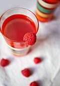 A glass of raspberry juice and fresh raspberries