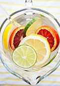 Various different citrus fruit slices in a jug of water