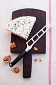 Blue cheese and walnuts on a chopping board with a knife