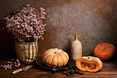 An arrangement featuring pumpkins, dried flowers, an old pair of scales, a bottle and a knife