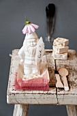 Stillleben mit weißem Gartenzwerg aus Porzellan und Blütenhut, beschriftete Feder, neben Besteck auf Schemel mit abblätternder Farbe