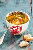 A cup of fish soup with prawns