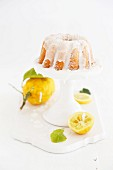 Lemon Bundt cake with light icing on a white cake stand