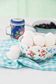 Eggs in a floral porcelain bowl on a checked napkin with egg shells next to it