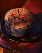 A chocolate soufflé in a dark grey baking tin