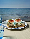 Buttermilk mousse and slices of bread topped with soused herring tartar on a table overlooking the sea