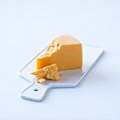 A slice of hard cheese on a plastic board