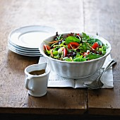 Green salad with tomatoes and a jug of vinaigrette