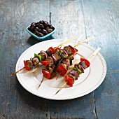 Lamb kebabs with pepper and onions served with a bowl of olives