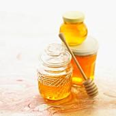Jars of honey and honey dipper