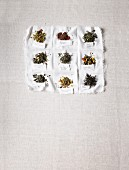 Various labeled teas on a white cloth