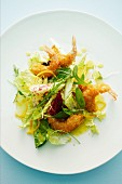 A mixed leaf salad with baked king prawns and an orange dressing