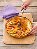 An apple tart with cinnamon being sliced