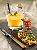 Cold carrot soup with a fried lobster skewer and mango salsa