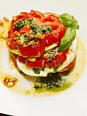 A beefsteak tomato with burrata, pesto and pine nuts