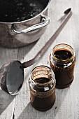 Powidl (stewed plums) in a saucepan and in jars
