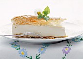 Slice of cheese cake topped with puff pastry and garnished with a sprig of mint and Daisy