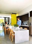 Küchentheke und tiefer gesetzter Essplatz aus Marmorplatten mit finnischen Stuhlklassikern in offener Küche